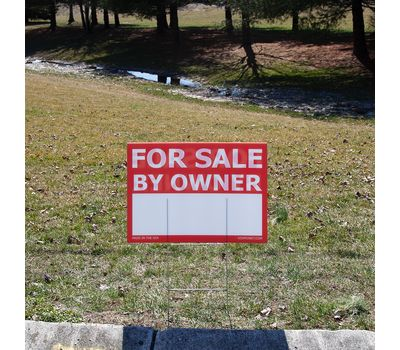 Sign staked into the ground in front of a yard